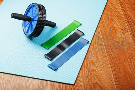Set of Roll for body muscles, elastic bands for fitness on a blue training Mat. Training at home and in the gym