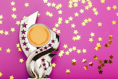 Superprize of gold with fireworks of stars on a pink background.