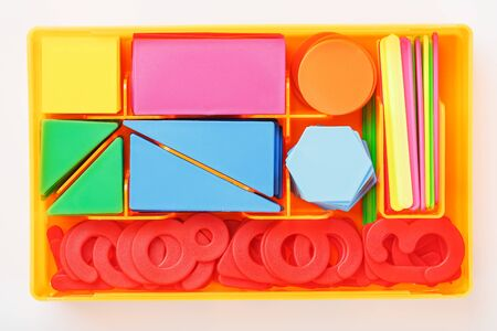 A box with Colorful plastic figures and numbers on a white background. Educational games for children. Math and calculation skills. The view from the top