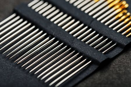 A set of sewing needles on a black background. A series of Golden needles