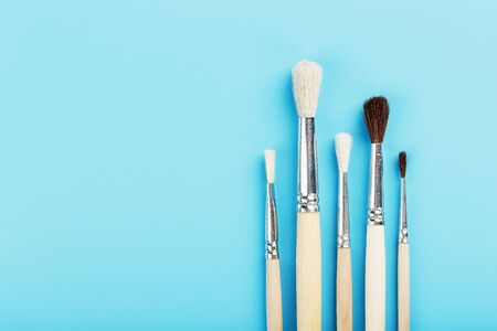 Brushes for drawing with paints made of natural wood and wool on a blue background. Free space