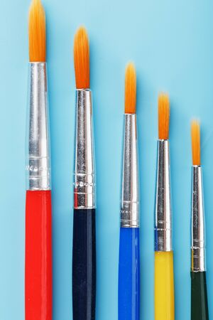 Multi-colored paint Brushes on a blue background. Free space