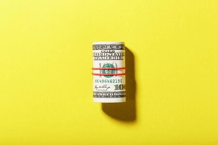 A roll of hundred-dollar American bills is tied with a red elastic band on a yellow background. Isolate. 100 dollars of currency