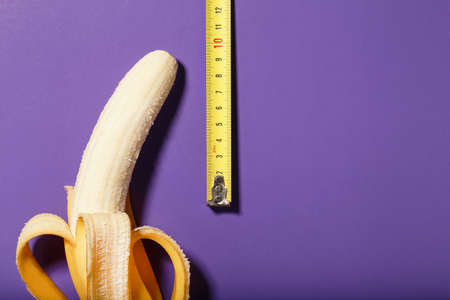Yellow banana penis concept measured by measuring tape on a purple background. Comparison of the size of a man's dignity. Free space