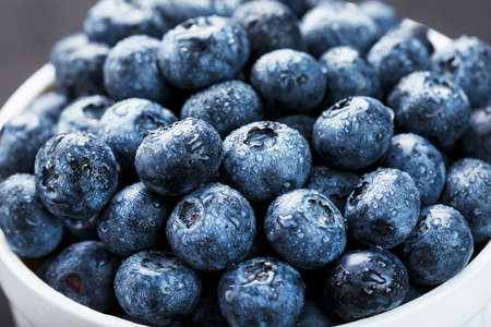 Blueberries in a white Cup on a black textured background.