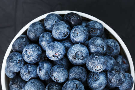 Blueberries in a white Cup on a black textured background. Juicy and ripe forest berry, healthy Food Concept.