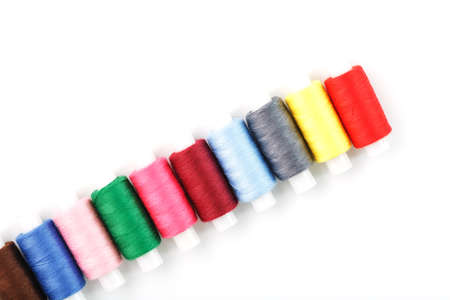 Sewing threads of different colors on reels on a white background. Free space, close-up. Isolate