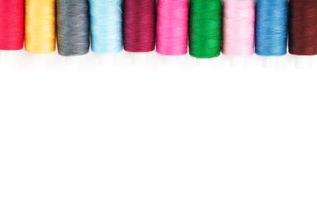 Colorful cotton craft sewing threads multicolored in a row isolated on a white background. Free space, isolate close-up Imagens