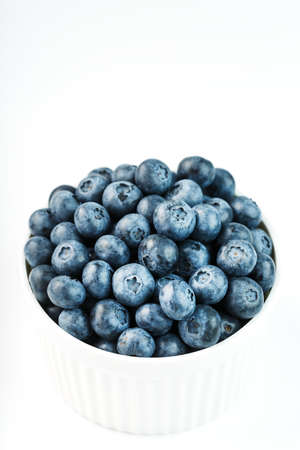 Blueberries are ripe berries in a white Cup on a white background.