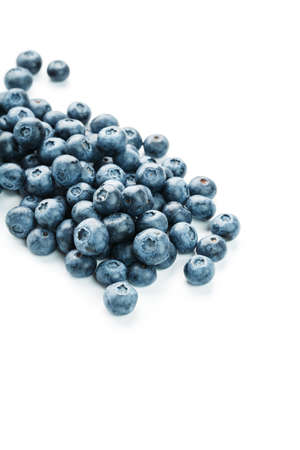 Tasty blueberries fruit are scattered on a white background.