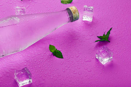 A bottle with an ice drink in drops of condensation, ice cubes and mint leaves on a pink background