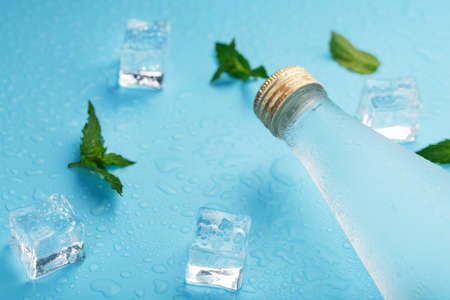 Cold Water Bottle, ice cubes, drops and mint leaves on a blue background. 免版税图像