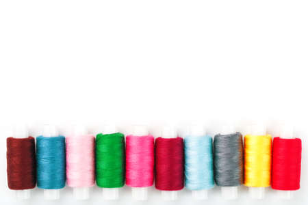 Colorful cotton craft sewing threads multicolored in a row isolated on a white background.