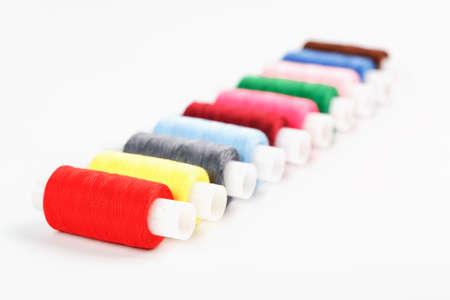 Sewing threads of different colors on reels on a white background. Free space, close-up. Isolate 版權商用圖片