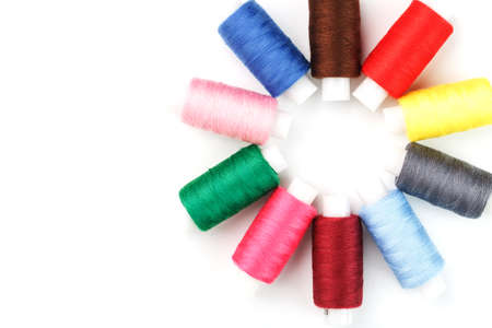 Sewing threads of different colors on reels on a white background in a circle.