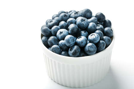 Blueberries in a white Cup on a white background. Isolate, free space