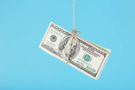Dollars are tied on a rope, on a blue background. Isolate, free space. 版權商用圖片