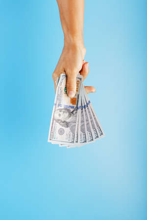 A hand with one hundred-dollar bills on a blue background. 版權商用圖片