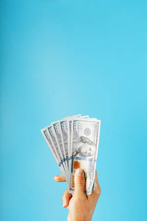 Wad of banknotes in hand on a blue background. The concept of financial assistance.
