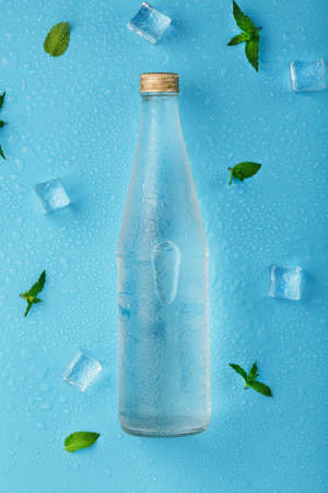 Cold Water Bottle, ice cubes, drops and mint leaves on a blue background. 版權商用圖片