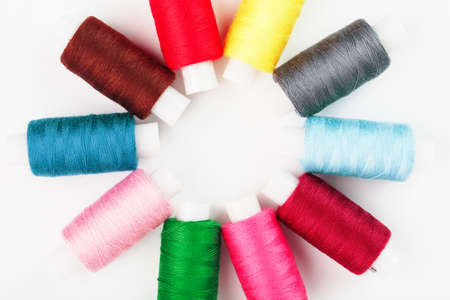 Sewing threads of different colors on reels on a white background in a circle. 版權商用圖片