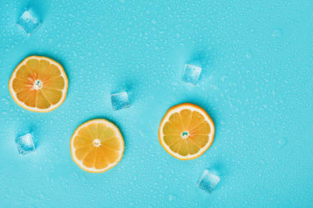 Slices of fresh orange on a blue background with ice. 版權商用圖片