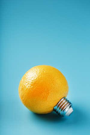Lemon fruit as a light bulb on a blue background. The conceptual idea. 版權商用圖片
