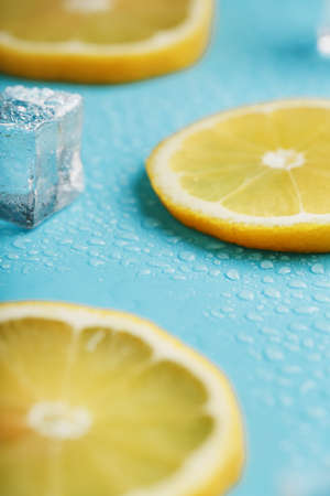 Fresh lemon with ice and drops on a blue background. 版權商用圖片