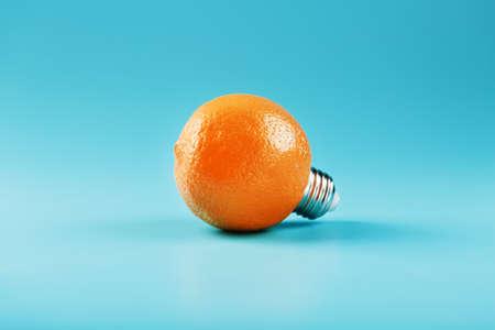 Orange light bulb on a blue background. The concept of fruit ideas