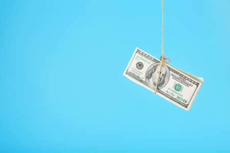 Money tied dollars on a rope, on a blue background. Isolate, free up space. 版權商用圖片