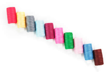 Sewing threads of different colors on reels on a white background. Free space, close-up. Isolate Standard-Bild