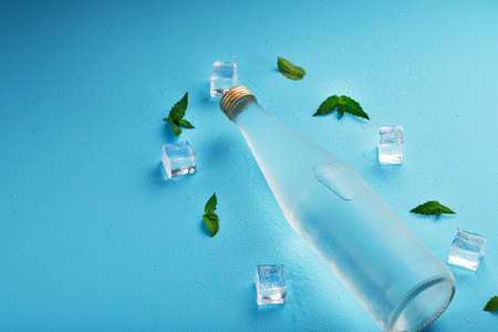 A bottle of ice water, ice cubes, drops and mint leaves on a blue background.
