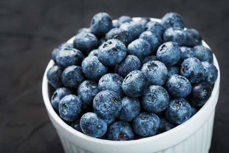 Organic blueberries in a white Cup on a black Board.