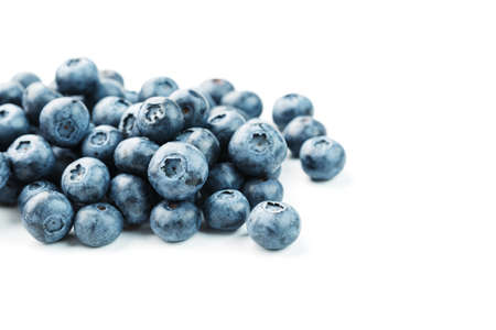 Blueberries are scattered on a white background. Free space, isolate. Studio light.
