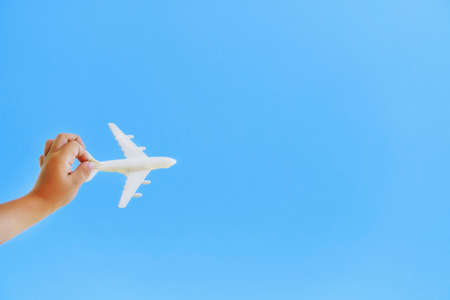 A white toy plane in a childs hand against a blue sky.