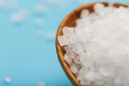 In a wooden spoon, sea salt crystals on a blue background, macro. Standard-Bild