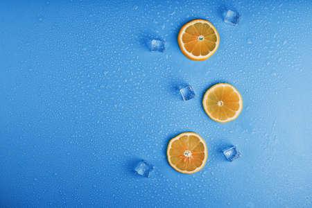 Slices of fresh orange on a blue background with ice. Standard-Bild