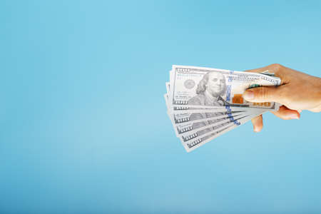 A hand with one hundred-dollar bills on a blue background. Standard-Bild