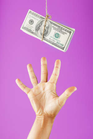 A hand tries to grab the money on a rope on a pink background. Standard-Bild