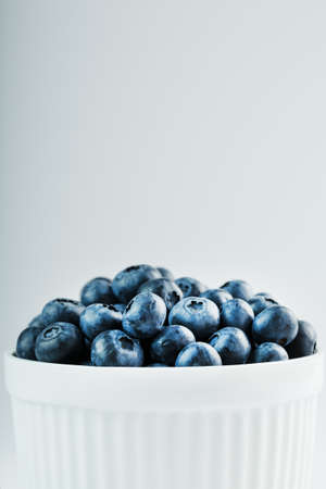 Juicy Blueberries in a white Cup on a white background.