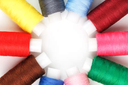 Sewing threads of different colors on reels on a white background in a circle. Standard-Bild