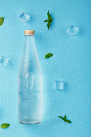 Bottle with an ice cold beverage, ice cubes, drops and mint leaves on a blue background.
