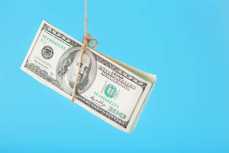 Money tied dollars on a rope, on a blue background. Isolate, free up space. Standard-Bild