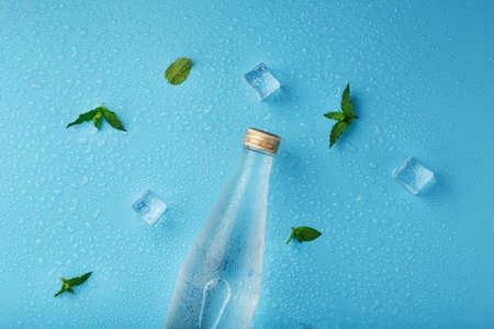 Cold Water Bottle, ice cubes, drops and mint leaves on a blue background. Standard-Bild