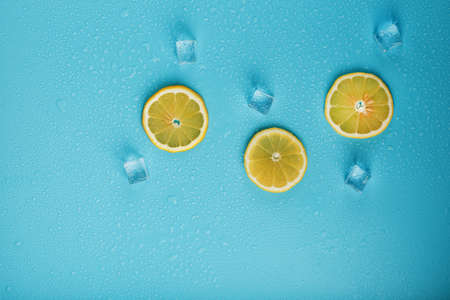 Slices of fresh lemon on a blue background with ice.