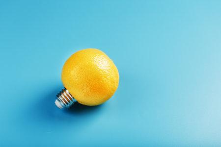 Lemon light bulb on a blue background. The fruit of a lemon with base from the bulb E27.