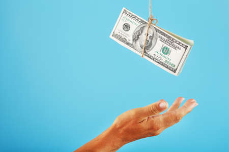 The palm reaches out to the money suspended on a rope, on a blue background.