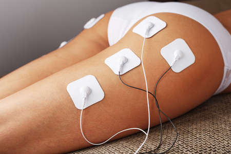 Myostimulation electrodes on the and legs of a woman in a beauty salon. Rehabilitation and treatment, weight loss.