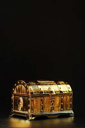 Gold treasure chest on a black textured background. Closed box with money and jewelry. Free space, Vertical frame Low key