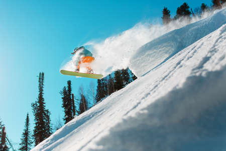 A snowboarder jumps from a high snow-covered springboard in a forest against a blue sky. Extreme sports Foto de archivo